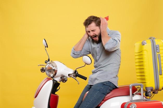 Vorderansicht des reisekonzepts mit dem verärgerten nervösen emotionalen jungen mann, der auf motorrad mit koffern auf ihm sitzt, die bankkarte auf gelb halten