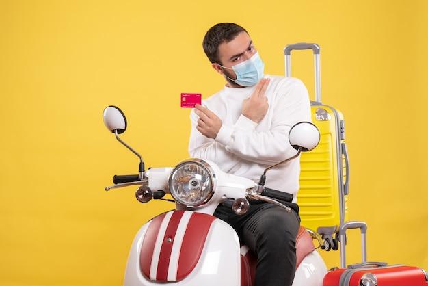Vorderansicht des reisekonzepts mit selbstbewusstem jungen mann in medizinischer maske, der auf einem motorrad mit gelbem koffer darauf sitzt und eine bankkarte hält