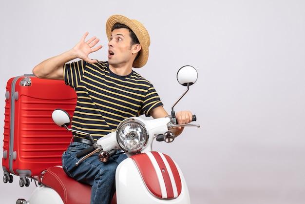 Vorderansicht des schockierten jungen mannes mit strohhut auf moped