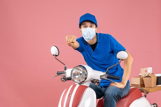 Vorderansicht des schockierten lieferboten in medizinischer maske mit hut, der auf einem roller auf pastellfarbenem pfirsichhintergrund sitzt