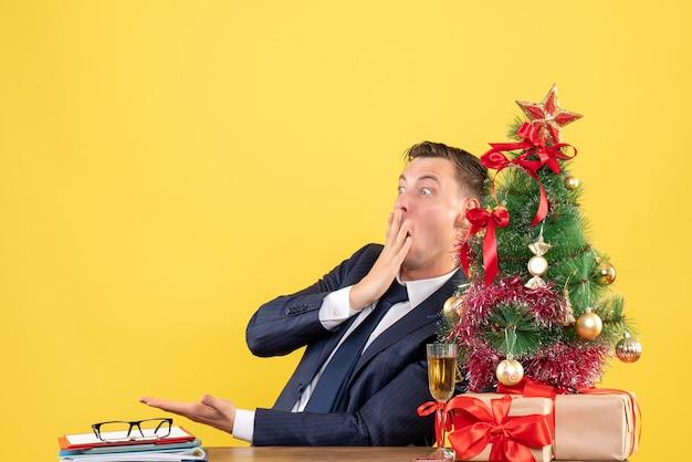 Vorderansicht des schockierten mannes, der am tisch nahe weihnachtsbaum sitzt und auf gelb präsentiert.