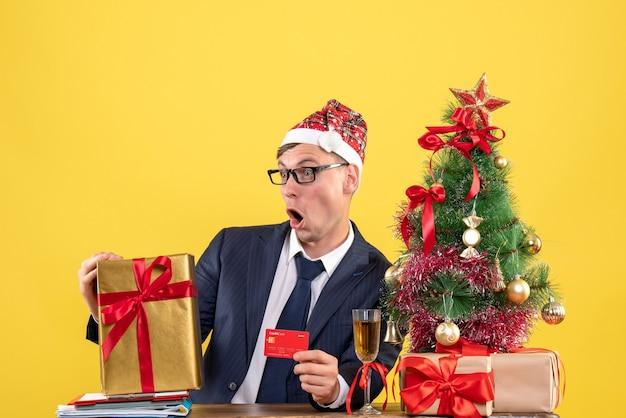 Vorderansicht des schockierten mannes, der karte hält, die am tisch nahe weihnachtsbaum sitzt und auf gelb präsentiert