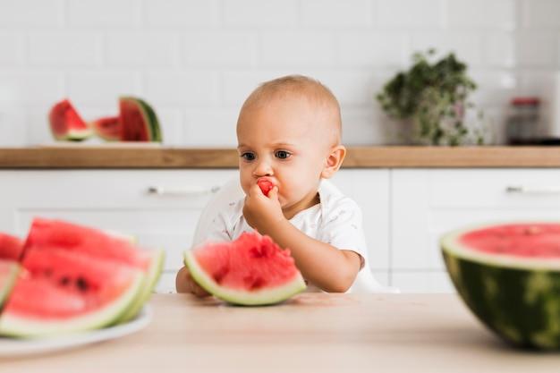 Vorderansicht des schönen babys, das wassermelone isst