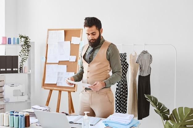 Vorderansicht des schönen männlichen modedesigners, der im atelier mit papieren arbeitet