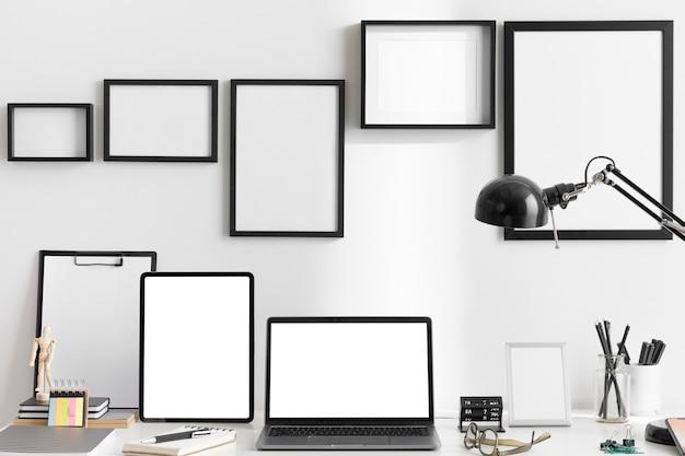 Vorderansicht des schreibtischs am arbeitsplatz mit lampe und laptop