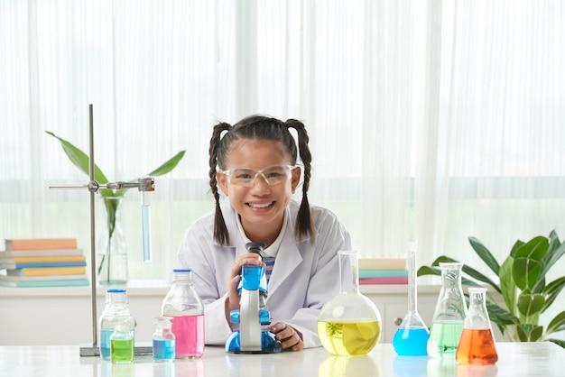 Vorderansicht des schulmädchens im laborkleid, welches das chemische experiment tut