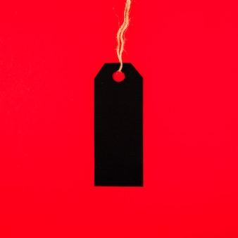 Vorderansicht des schwarzen aufklebers auf rotem papier