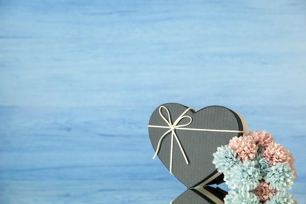 Vorderansicht des schwarzen herzförmigen kastens farbige blumen auf blau mit