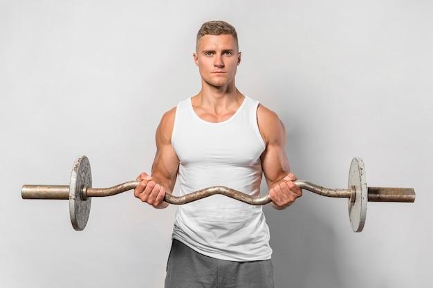 Vorderansicht des sehr fitten mannes, der beim halten von gewichten aufwirft