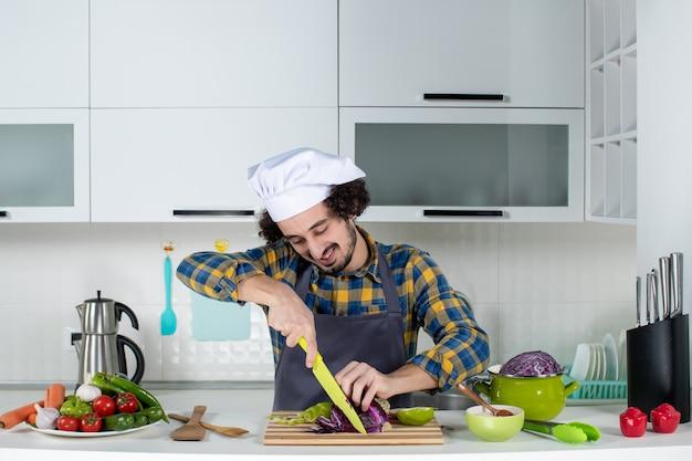 Vorderansicht des selbstbewussten kochs mit frischem gemüse, das lebensmittel in der weißen küche hackt