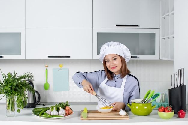 Vorderansicht des selbstbewussten kochs und des frischen gemüses mit kochausrüstung und dem mischen des eies in eine weiße schüssel in der weißen küche