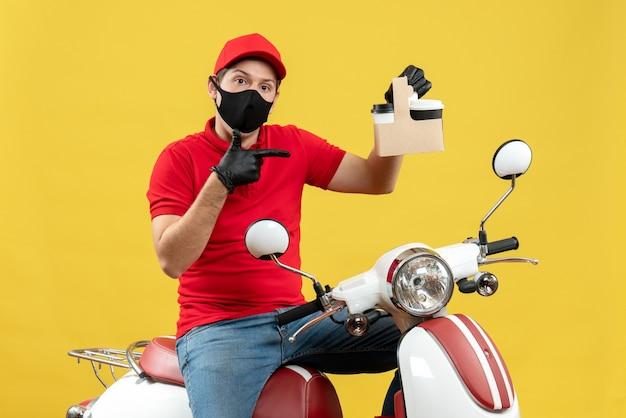 Vorderansicht des selbstbewussten kuriermannes, der rote bluse und huthandschuhe in der medizinischen maske trägt, die auf roller sitzt, der befehle zeigt