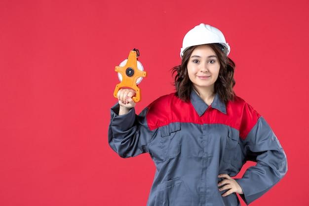 Vorderansicht des selbstbewussten weiblichen architekten in der uniform mit dem schutzhelm, der maßband auf isolierter roter wand hält