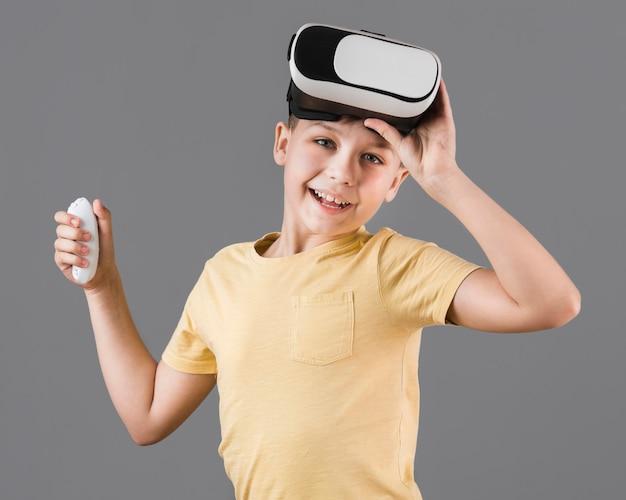Vorderansicht des smiley-jungen, der virtual-reality-headset trägt
