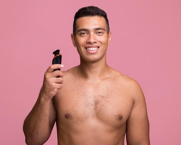 Vorderansicht des smiley-mannes, der einen elektrischen rasierer hält