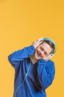 Vorderansicht des smiley-mannes, der musik auf kopfhörern hört