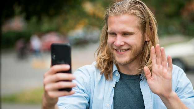 Vorderansicht des smiley-mannes, der selfie im freien nimmt