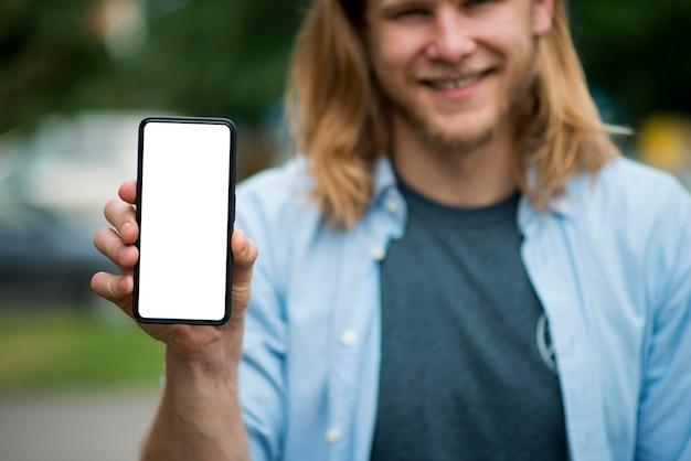 Vorderansicht des smiley-mannes, der smartphone hält
