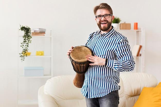 Vorderansicht des smiley-mannes mit trommel zu hause Kostenlose Fotos