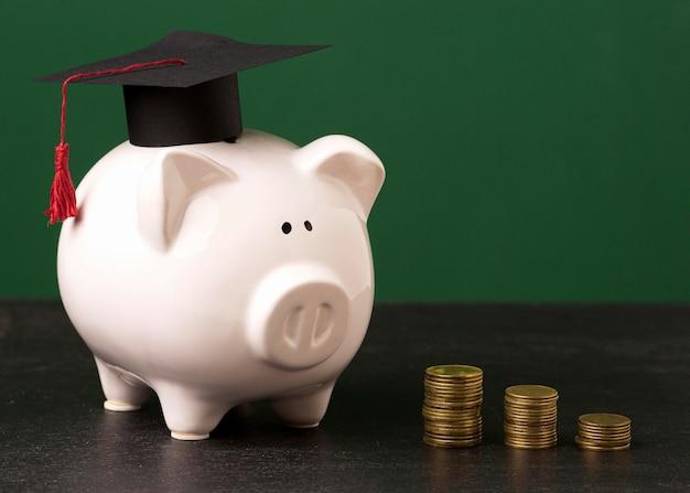Vorderansicht des sparschweins mit akademischer kappe und münzen
