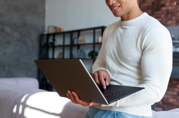 Vorderansicht des stehenden mannes, der laptop verwendet