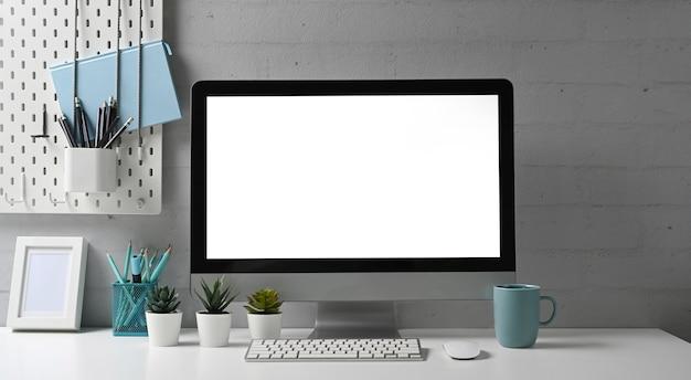 Vorderansicht des stilvollen arbeitsbereichs mit modellcomputer- und büromaterial-gadget. leerer bildschirm für die montage des grafikdisplays.