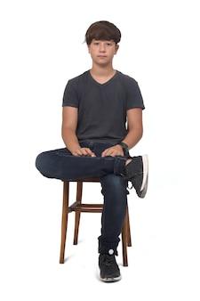 Vorderansicht des teenagers, der auf einem stuhl mit weiß sitzt
