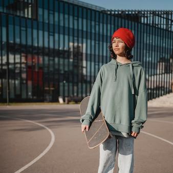 Vorderansicht des teenagers mit skateboard und kopierraum