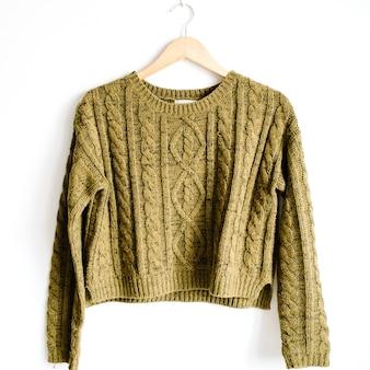 Vorderansicht des trendigen grünen weiblichen pullovers der schönheit auf kleiderbügel in der nähe von weißem hintergrund. mode-konzept.