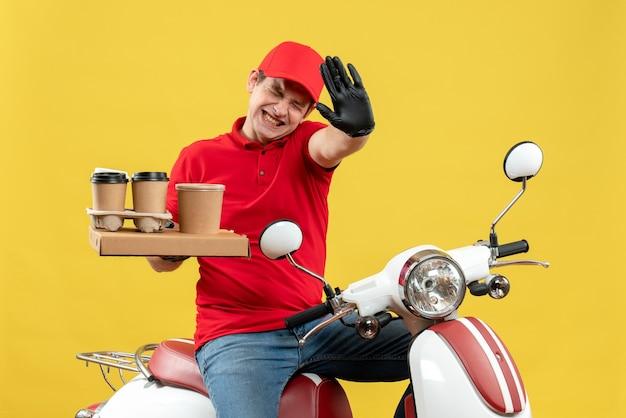 Vorderansicht des unruhigen nervösen kuriermannes, der rote bluse und huthandschuhe in der medizinischen maske trägt, die befehl liefert, der auf roller hält, der befehle hält