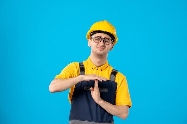 Vorderansicht des unzufriedenen männlichen arbeiters in der gelben uniform, die t zeichen auf blauer wand zeigt