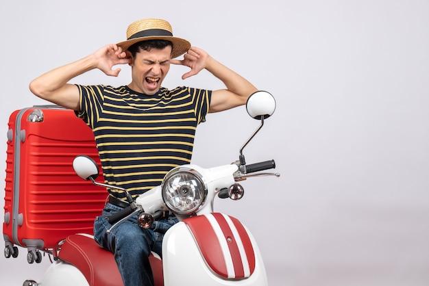 Vorderansicht des verärgerten jungen mannes mit strohhut auf moped, das augen mit händen bedeckt