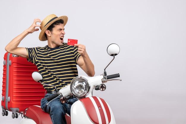 Vorderansicht des verärgerten jungen mannes mit strohhut auf moped, das bankkarte hält