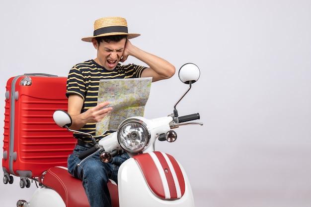 Vorderansicht des verärgerten jungen mannes mit strohhut auf moped, das karte und ohr hält