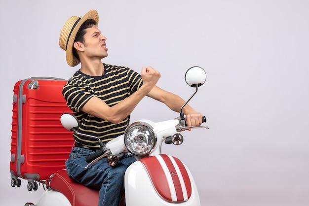 Vorderansicht des verärgerten jungen mannes mit strohhut auf moped, der schlag zeigt