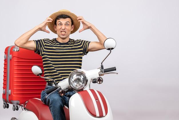 Vorderansicht des verärgerten jungen mannes mit strohhut auf moped