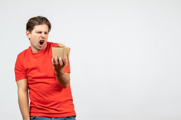 Vorderansicht des verärgerten nervösen jungen kerls in der roten bluse, die kleine box auf weißem hintergrund hält
