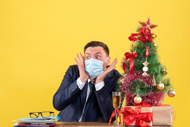 Vorderansicht des verblüfften geschäftsmannes, der am tisch nahe weihnachtsbaum sitzt und auf gelbem wandfreiraum präsentiert