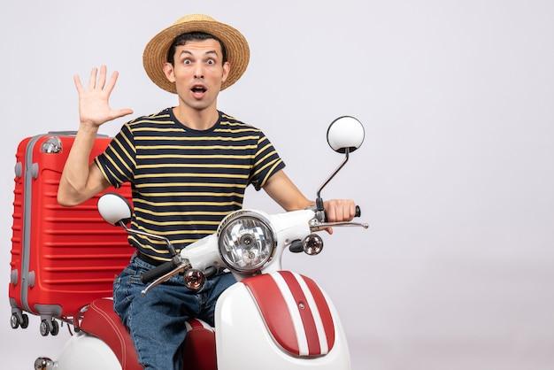 Vorderansicht des verblüfften jungen mannes mit strohhut auf moped winkende hand