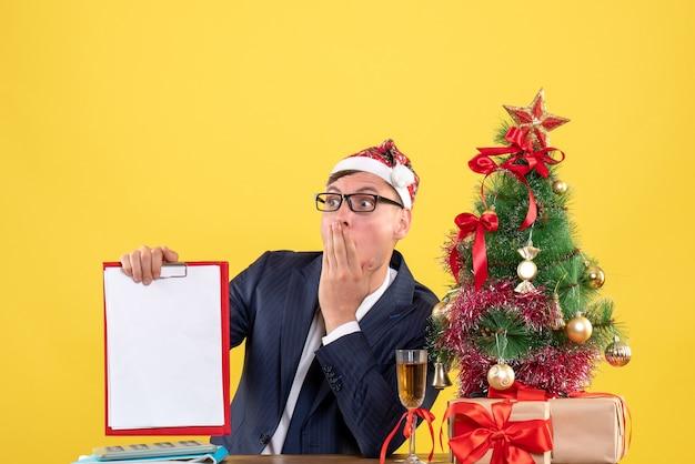 Vorderansicht des verblüfften mannes, der klemmbrett hält, das am tisch nahe weihnachtsbaum sitzt und auf gelber wand präsentiert