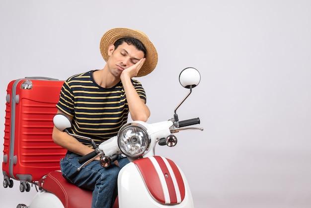 Vorderansicht des verschlafenen jungen mannes mit strohhut auf moped