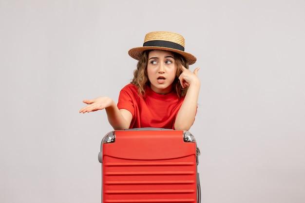 Vorderansicht des verwirrten feiertagsmädchens mit ihrem koffer, der auf weißer wand steht