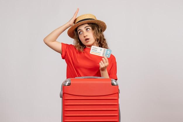 Vorderansicht des verwirrten feiertagsmädchens mit ihrem valise holding ticket