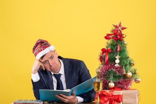 Vorderansicht des verwirrten geschäftsmannes, der am tisch nahe weihnachtsbaum sitzt und auf gelb präsentiert
