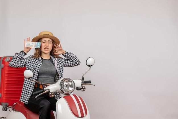 Vorderansicht des verwirrten jungen mädchens auf moped, das ticket auf grauer wand hält