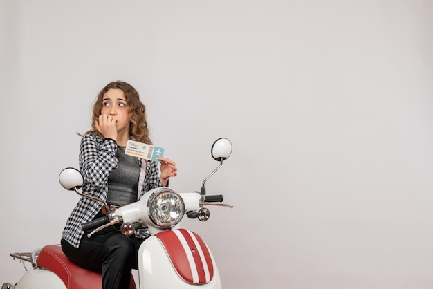 Vorderansicht des verwirrten jungen mädchens auf moped, das ticket hält