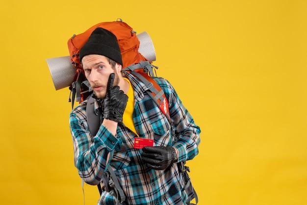Vorderansicht des verwirrten jungen mannes mit backpacker, der rabattkarte hält