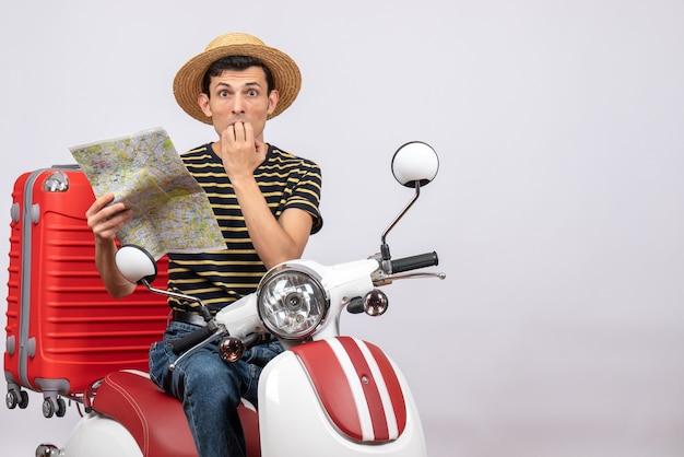 Vorderansicht des verwirrten jungen mannes mit strohhut auf moped, das karte betrachtet kamera betrachtet