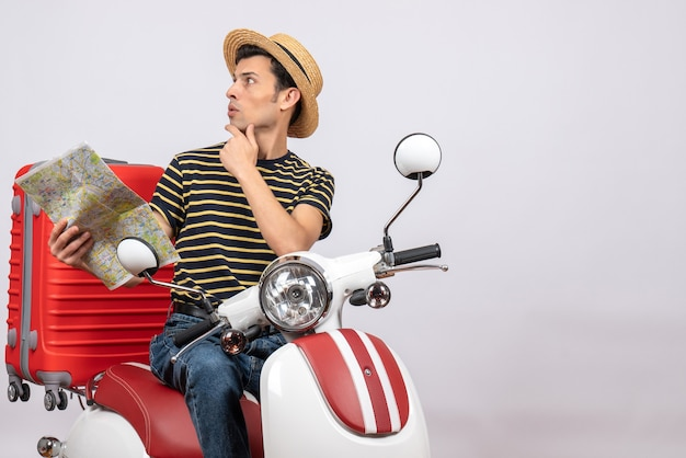Vorderansicht des verwirrten jungen mannes mit strohhut auf moped, das karte hält, die etwas schaut