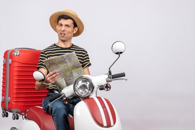 Vorderansicht des verwirrten jungen mannes mit strohhut auf moped, das karte hält